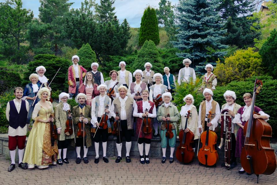 the kamloops brandenburg orchestra posing in period baroque costumes in a garden area